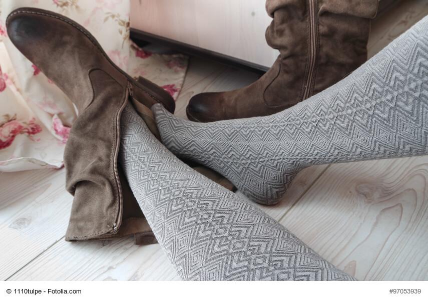Frau zieht Schuhe aus – Herbst- & Wintermode